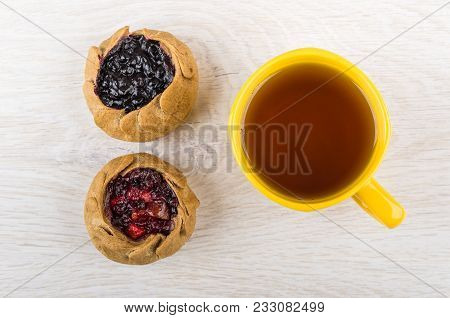 Pies With Blueberries, Cowberries And Tea In Yellow Cup On Wooden Table. Top View
