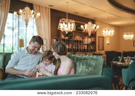 Young family with a gift in a restaurant