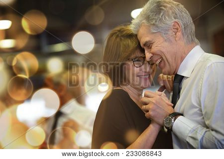 Romantic senior couple dancing together at dance hall