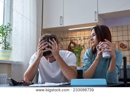 A Young Couple Sits At A Table In The Kitchen And Analyzes The Family Budget. The Financial Crisis I