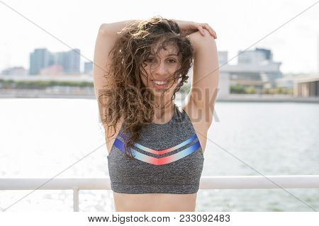 Happy Sporty Girl In Sport Bra Exercising On Quay With City And River In Background. Tired Fit Girl
