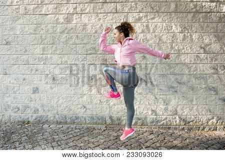 Joyful Sporty Latin Girl Jumping High And Raising Knee. Street Dancer Warming Up Intensively Before