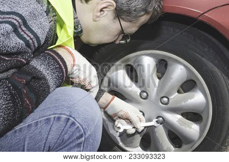 A Man In A Safety Vest Is Changing A Wheel In His Car On The Side Of The Road