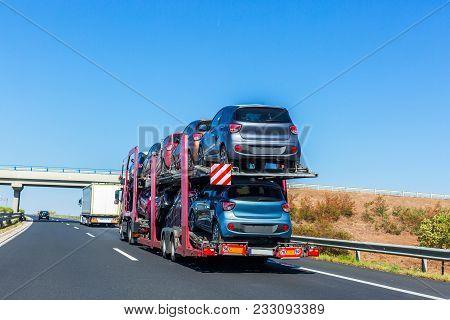 Car Carrier Trailer With Cars On Bunk Platform. Car Transport Truck On The Highway. Highway Bridge.