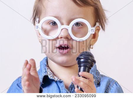 The Famous Actress. Humorous Photo Of Cute Child Girl Singing With A Microphone (happy Childhood, Te