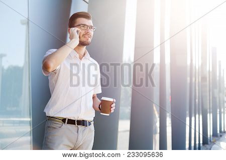 Attractive Pensive Businessman Or Lawyer In Eyeglasses Is Talking On Cell Phone And Drinking Coffee