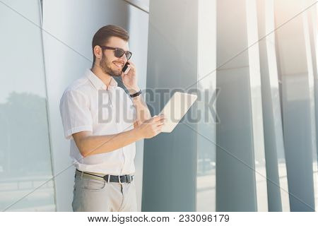 Attractive Smiling Businessman In Sunglasses Is Holding Digital Tablet And Talking On Mobile Phone W