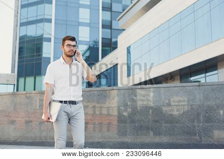 Pensive Businessman Is Talking On Cell Phone And Holding Digital Tablet In His Hand While Standing I
