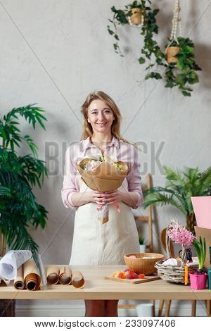 Photo of smiling florist in apron with bouquet of flowers with kraft paper