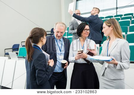 Female and male executives holding coffee cups while standing in lecture hall
