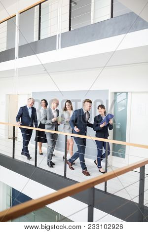 Full length of confident business people discussing while walking on corridor by railing in office
