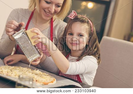 Mother And Daughter In The Kitchen Making Pizza; Daughter Grating Cheese On The Top Before Baking. F