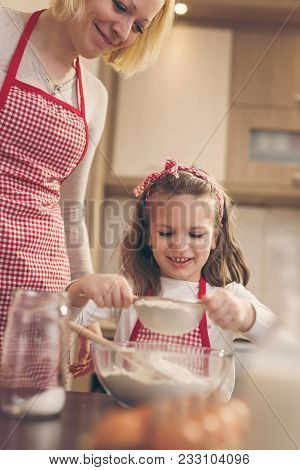Mother And Daughter Sowing Flour Through The Sieve Into A Bowl. Mother Teaches Daughter To Knead A D