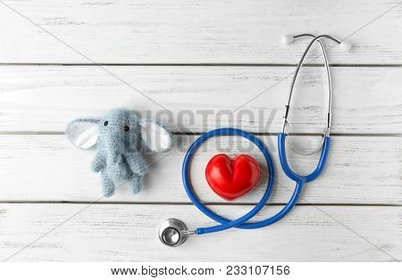 Cute knitted elephant, small heart and stethoscope on white wooden background. Concept of visiting children's doctor