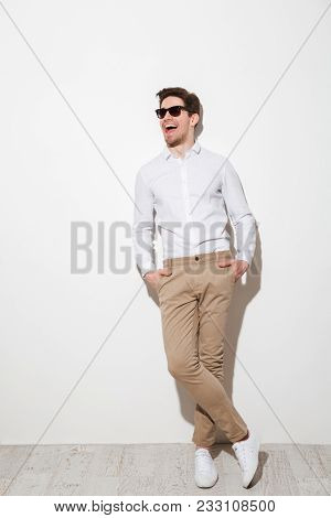 Full length picture of optimistic man dressed in casual clothing and sunglasses posing on camera with hands in pockets and laughing over white background with shadow