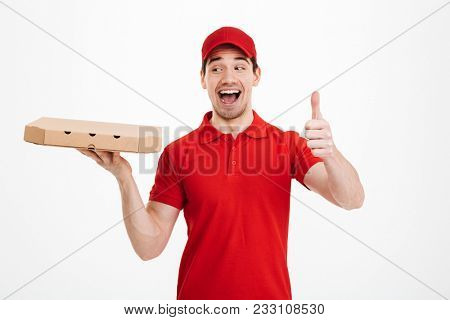 Delivery man 25y in red t-shirt and cap holding takeaway carton box with pizza and gesturing thumb up with perfect smile isolated over white background