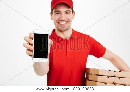 Photo closeup of affable man from delivery service in red t-shirt and cap holding stack of pizza boxes and showing copyspace screen of cell phone isolated over white background