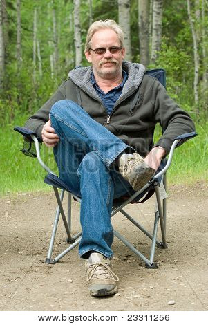 Man In Camping Chair Outside