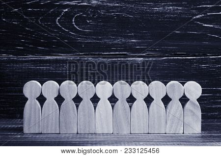 Wooden Figures Of People Stand In A Row In The Formation On The Background Of Ebony. The Concept Of