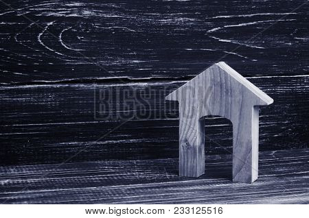 Figurine Of A Wooden House With A Large Doorway On A Background Of Black Boards. Concept Of Real Est