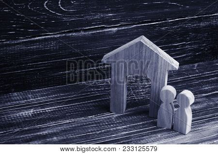 Figurine Wooden House With Two People Side By Side On A Background Of Black Boards. Concept Of Real
