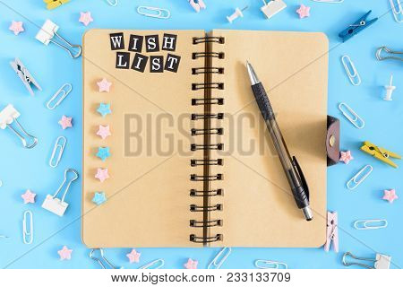 Open Notebook On Springs With An Inscription Wish List. Stationery Razrosannye On A Blue Background.