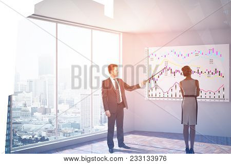 Businessman And Woman In Modern Office Interior With Forex Chart On Whiteboard And City View. Presen