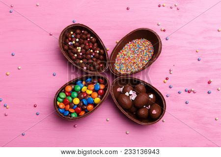 Chocolate Easter Eggs And Colorful Candies On A Bright Pink Background. Easter Sweets Concept.