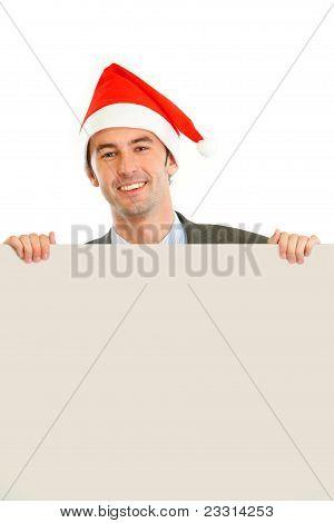 Smiling Guy In Santa Hat Holding Blank Billboard