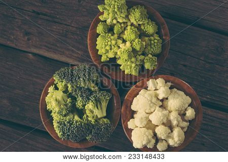 Top View Of Fresh Pieces Of Romanesco Broccoli, Broccoli And Cauliflower In Small Rustic Wooden Bowl