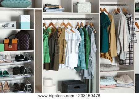 Large wardrobe closet with different clothes, shoes and accessories