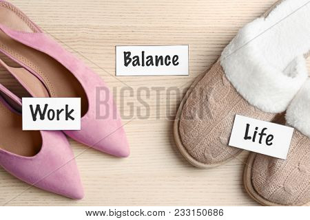 Words WORK, LIFE, BALANCE and women's footwear on wooden background