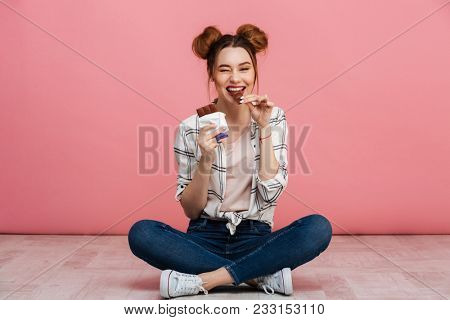 Portrait of a cheerful young girl eating chocolate bar while sitting on a floor with legs crossed isolated over pink background