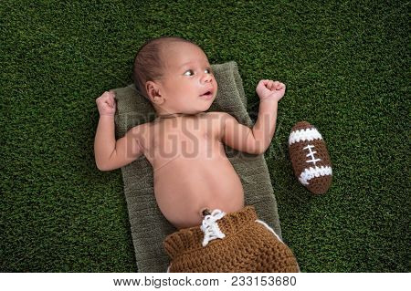 A Two Week Old, Alert, Newborn Baby Boy Lying On Grass Turf With A Crocheted American Football.