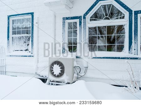 Heat pump outside a residential home in winter.