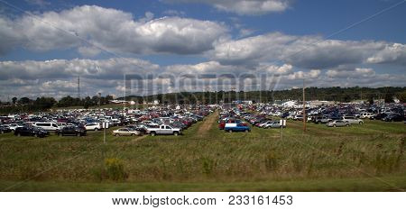 Numerous Cars And Trucks Parked In A Grass Field Parking Lot For A County Fair Under A Cumulus Cloud