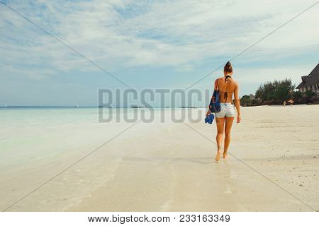 View From Back Young Woman With A Backpack Walking Along Ocean Shoreline In The Morning