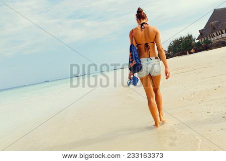View From Back Young Tanned Woman With Backpack Walking Along Ocean Shoreline In The Morning