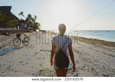 Young Woman With A Backpack Walking Along Ocean Shoreline At Sunset. View From The Back