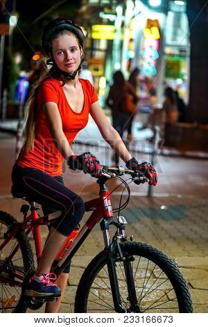 City night bicycle ride. Girls wearing bicycle helmet. Nightlife and passer people in city background. Luminous windows and group people in background.