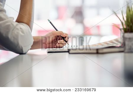 Close Up Short Of Businessman Hand Holding Pencil While Sitting At White Desk At Workplace