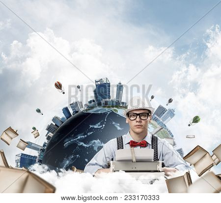 Young Man Writer In Hat And Eyeglasses Using Typing Machine While Sitting At The Table With Flying B