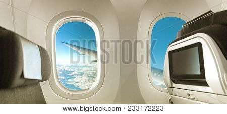 Plane interior with window and seats banner panorama background for advert. Airplane cabin view of wing during flight travel vacation. Empty inside economy class.