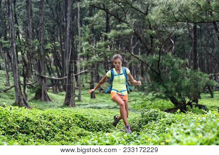 Trail runner woman athlete running jumping in forest nature mountains background. Sport girl active training difficult cardio workout outdoor in summer landscape. Focus and endurance, poster