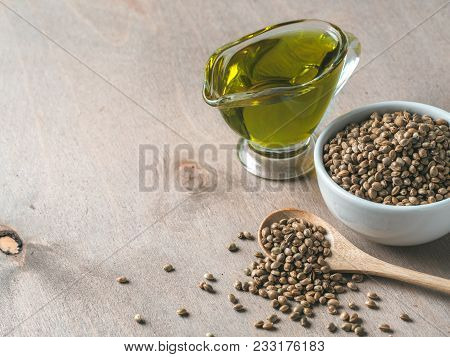 Hemp Seeds And Hemp Oil On Brown Wooden Table. Hemp Seeds In Wooden Spoon, In Small Bowl And Hemp Oi