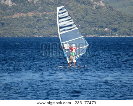 Windsurfing In The Sea. Picturesque Landscape With Windsurfer, Mountain Wooded Shore And Boats In Ha