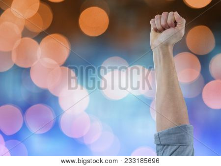Digital composite of Hand arm celebrating with fist and sparkling light bokeh background
