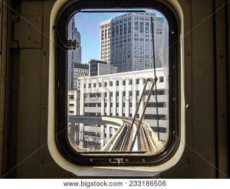 Morning Commute In The City. View Through Tram Window Of The City Skyline And Train Tracks Detroit,