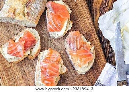 Finger Food. Appetizer Canapes Sandwiches With Baguette, Salmon And Butter On Rustic Wooden Board Ov