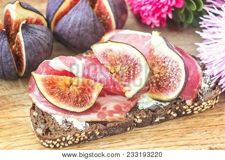 Sandwiches With Ricotta Cheese, Fresh Figs And Ham, Bacon Ham Prosciutto On Rustic Wooden Cutting Bo